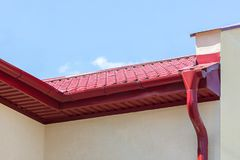 Piova la grondaia con l'incanalamento rosso del metallo sul tetto della casa Fotografia Stock