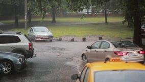 Piova piovere a dirottoe sulla pavimentazione, su un taxi e sui giri delle automobili nell'inondazione Un'altra automobile passa  stock footage