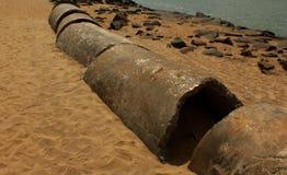 Pipas abandonadas del cemento en la arena de la playa imágenes de archivo libres de regalías