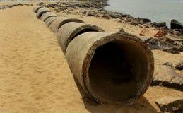 Pipas abandonadas del cemento en la arena de la playa fotos de archivo libres de regalías