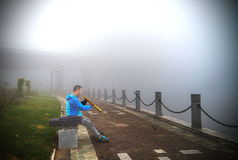 Pipblåsareman i morgondimma, Chifeng stad, Kina royaltyfri fotografi