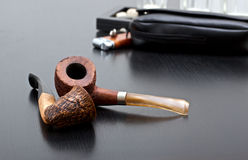 Pipe. Two briar pipe on sofa with accessories Royalty Free Stock Images