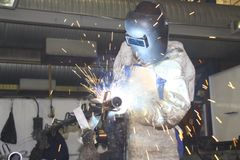 Pipe being welded by worker. Man welding a metal tube, wearing protective gear and apron. Also showing the blue hue of brilliant light from the arcs and the Royalty Free Stock Images