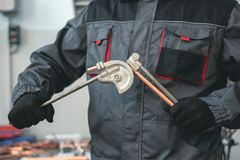 Pipework. Pipe bender tool in a hands of factory worker on a factory workbench background. Fitter is bending a pipe. Pipework stock photo