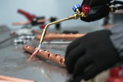 Pipe brazing lamp. Worker is soldering a pipe by a blow lamp on a factory workbench background. Pipework stock images