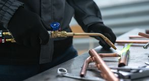 Pipe brazing lamp. Worker is soldering a pipe by a blow lamp on a factory workbench background. Pipework royalty free stock photography