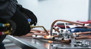 Pipe brazing lamp. Worker is soldering a pipe by a blow lamp on a factory workbench background. Pipework stock photos