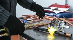 Pipe brazing lamp. Worker is soldering a pipe by a blow lamp on a factory workbench background. Pipework royalty free stock images