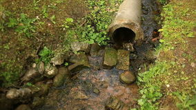 A pipe of a broken water pipe sticking out of the ground. From it flows a stream. stock video footage
