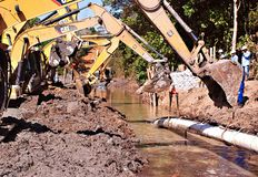 Pipe Burying Operation Into Swamp. Y Area,, supported by various excavators royalty free stock photography