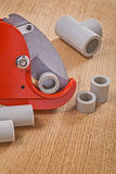 Pipe cutter with cutted pipes on wooden boards close up Royalty Free Stock Photos