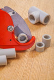 Pipe cutter and polypropylene cutted pipes on wooden boards Stock Image