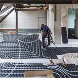 Pipe fitter mounting underfloor heating. Royalty Free Stock Images