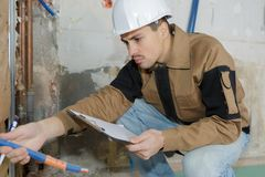 Pipe fitter reading manual. Pipe fitter reading the manual Stock Images