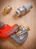 Pipe fixtures and monkey wrench on wooden board close up Stock Photo