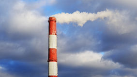 Pipe industrial chimney with smoke against the sky and clouds Royalty Free Stock Photo