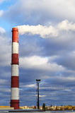 Pipe industrial chimney with smoke against the sky and clouds Royalty Free Stock Photos
