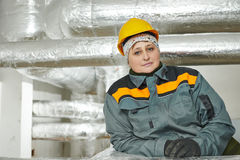 Pipe isolation worker. Thermal insulation. Female insulation worker in front of  by glass wool and foil industrial pipes Stock Photos