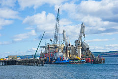 Pipe laying ship. Apache 2 a pipe and  cable laying ship surrounded by heavy cranes berthed by the jetty at Invergordon, Ross-shire. Heavy Engineering at sea Stock Images