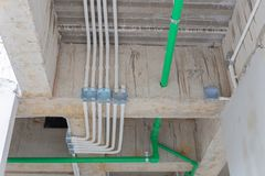 Pipe line water and galvanized steel conduits and upvc pipes for. Cable wiring joint with electrical box on cement ceiling at construction in new building stock photography