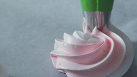 Pipe the meringue out onto the prepared baking sheet using a star tip stock video footage