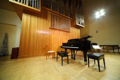 Pipe organ and concert grand piano in hall Stock Photo