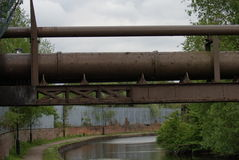 Pipe over Canal in East Manchester Royalty Free Stock Photos