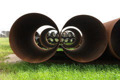 In  pipe plant. Big iron pipes on a green grass Stock Photography