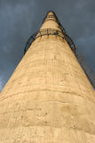 Pipe plant on the background of a stormy sky. Bottom view. Factory chimney with ladder on a background of a stormy sky. Bottom view Stock Photo