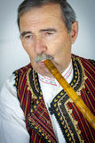 Pipe player in traditional clothing Stock Image