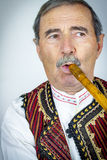 Pipe player in traditional clothing Stock Images