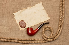 Pipe and rope with old paper. Pipe, old paper with a wax seal and rope on canvas of burlap stock photos