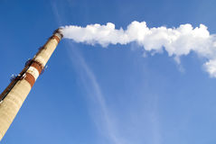 Pipe with smoke. Large pipe with smoke on blue sky Royalty Free Stock Images
