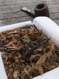 Pipe tobacco English Mixture in open box and pipe in the backgro. Und on wooden table Royalty Free Stock Photography