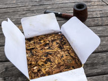 Pipe tobacco English Mixture in open box and pipe in the backgro. Und on wooden table Royalty Free Stock Photo