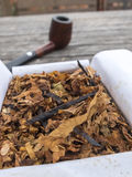 Pipe tobacco English Mixture in open box and pipe in the backgro. Und on wooden table Royalty Free Stock Photos