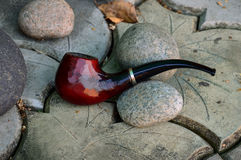 Pipe tobacco is on a gray rock. Smoking pipe Stock Image