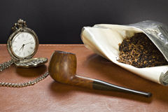 Pipe, tobacco and the old clock. Pipe,  tobacco and an old clock standing on a leather plan Stock Photography
