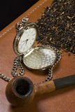Pipe, tobacco and the old clock. Pipe,  tobacco and an old clock standing on a leather plan Stock Photos