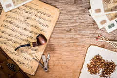 Pipe, tobacco, old money and notes Stock Photography