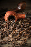 Pipe on tobacco pile Stock Photo