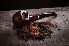 Pipe and tobacco on wooden surface Royalty Free Stock Image
