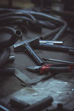 Pipe and tools on a work surface in a metalwork manufacturing. Vertical photo Stock Photos