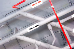 Pipe under the modern building. White and red pipe under the modern building Stock Photos