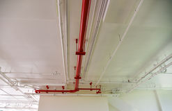 Pipe under the modern building. White and red pipe under the modern building Royalty Free Stock Photos