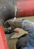 Pipe welder. A welder upsidedown welding a steam pipe stock image
