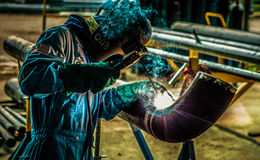 The Pipe Welder. A pipe welder at a construction workshop stock photo