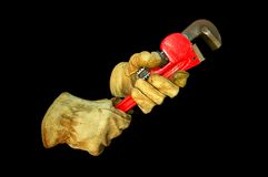 Pipe wrench. A worn pair of leather work gloves holding a red pipe wrench.  Clipping path is included in image.  Isolated on a black background Royalty Free Stock Image