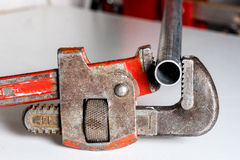 Pipe wrench in action on a workbench Stock Photo