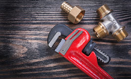 Pipe wrench brass equal tee nipple hose connector on wooden back Stock Images